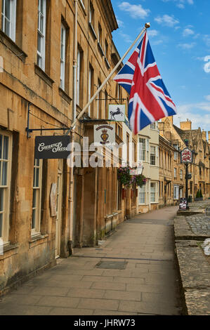 Chipping Campden High Street and a Union Jack flag flying from the from of a stone building in the Cotswold market - Stock Image