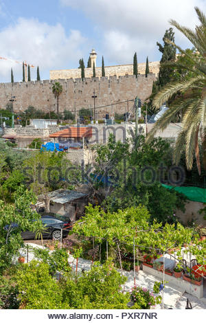 Contrasts of 21st century Jerusalem: Modern car and housing, gardens, electricity, ancient walls, construction crane - Stock Image