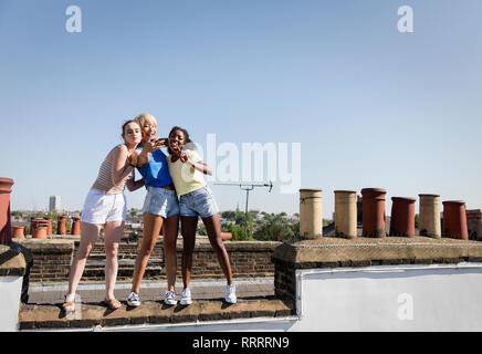 Young women friends taking selfie with camera phone on sunny rooftop - Stock Image