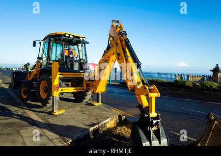 Workman using a JCB excavator extending a small lay-by on a  town centre site at Saltburn by the Sea - Stock Image