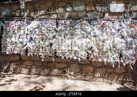 Wishing wall with tied note petitions to the Virgin Mary saint and Mother of God at her restored house near Ephesus - Stock Image
