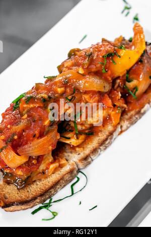 portuguese caldeirada de peixe spicy tomato onion and peppers fish stew on rustic tiborna toast tapas style - Stock Image