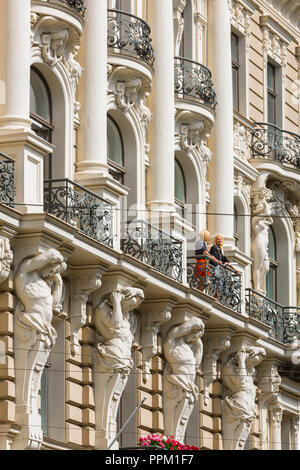 Riga art nouveau architecture, view of two women standing on the balcony of a building in Elizabetes Iela in the the Art Nouveau district of Riga. - Stock Image