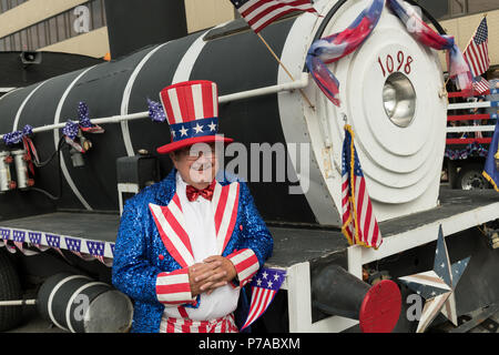 Anchorage, Alaska. 4th July, 2018. A man dressed as Uncle Sam stands by a parade float decorated as a steam train engine during the annual Independence Day parade July 4, 2018 in Anchorage, Alaska. Credit: Planetpix/Alamy Live News - Stock Image