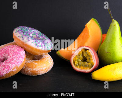 Donuts and fruit showing healthy and unhealthy foods - Stock Image