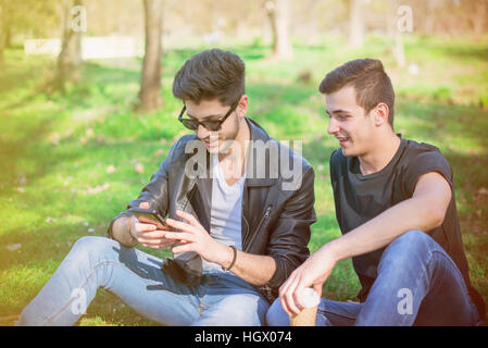 Smiling friends with smartphones sitting on grass in park - Stock Image