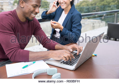Smiling young man using laptop on balcony - Stock Image