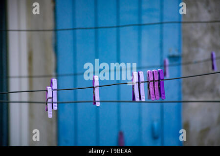 Clothespins on washing rope, hanging outside in small Provencal village in lavender color nd blue door - Stock Image