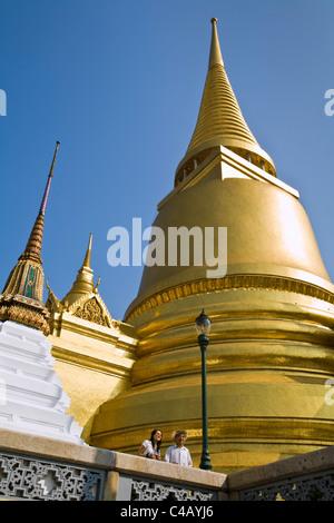 Thailand, Bangkok. The Phra Si Rattana chedi towers above tourists at Wat Phra Kaew (Temple of the Emerald Buddha). - Stock Image