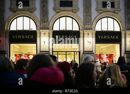Milan, Italy - December 7, 2018: crowd of people shop for Christmas gifts in front of the Versace boutique store windows in Galleria Vittorio Emanuele - Stock Image