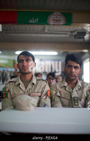HELMAND PROVINCE, Afghanistan (August 26, 2018) – Soldiers with the Afghan National Army (ANA) 215th Corps await the start of a graduation ceremony for a train-the-trainer course at the Regional Military Training Center on Camp Shorabak. The nearly month-long course taught instructors the basics of warrior training so they can, in turn, teach the upcoming classes of the new ANA Territorial Force who will assist in providing safe and secure elections to the people of Helmand and Nimroz provinces this October. (U.S. Marine Corps photo by Sgt. Sean J. Berry) - Stock Image