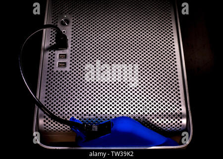 A bright blue external hard drive storage device plugged into a USB port on the front of an Apple Mac Pro desktop computer. - Stock Image