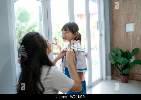 mother help her toddler kid preparing for school in the morning. young kindergarten student wearing school uniform - Stock Image
