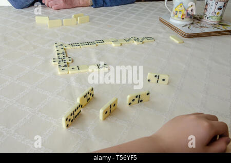 A close up view of a game of dominoes on a dining room table. - Stock Image
