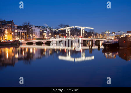 Skinny Bridge (Magere Brug) in Amsterdam, the Netherlands, and reflection in the river Amstel at night. - Stock Image