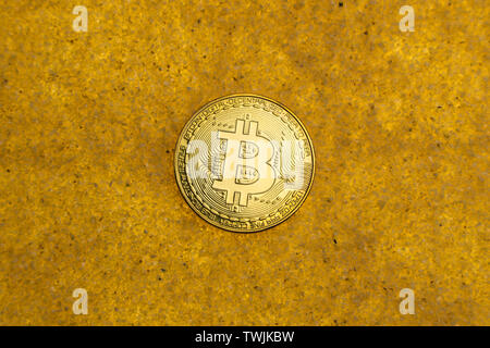 one bitcoin crypto coin on a shiny golden sand background with backlight, top view. - Stock Image