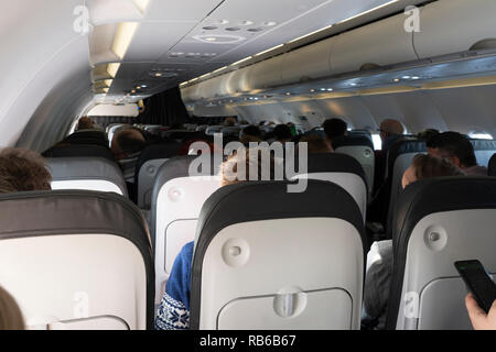Passengers sitting on a British Airways passenger jet in the afternoon flying to Vienna - Stock Image