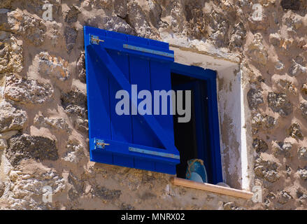 Close up view of a window frame and shutter with stone wall in Mallorca, Spain. - Stock Image