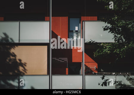 Red and gray modern facade of contemporary residential building with two rows of balconies of matte white glass - Stock Image