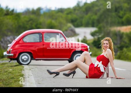 Young woman legs heels stiletto shoes Black with White dots smiling looking at camera - Stock Image