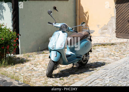 A sky blue colour Vespa 'city roller' scooter on a cobbled street in Stein an der Donau, Lower Austria - Stock Image