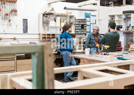 A group of mixed race carpenters discussing a project at a work station in a large woodworking shop. - Stock Image