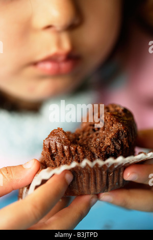 Five year old girl eats chocolate muffin - Stock Image
