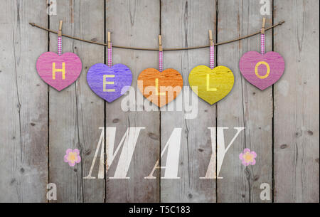 Hello May written on hanging pink and orange and purple hearts and weathered wooden background, with flowers - Stock Image