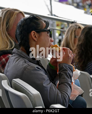 Woman spectator sitting in grandstand eating a pasty. Royal Highland Show 2018, Ingliston, Edinburgh, Scotland, United Kingdom, Europe. - Stock Image