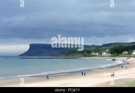 Walkers on the sandy Ballycastle beach with dark cliffs formed of basalt columns at Fair Head in the background. Ballycastle, Antrim, Northern Ireland - Stock Image