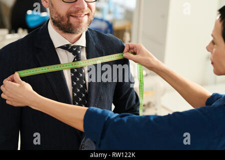 Tailor working with client - Stock Image