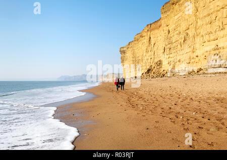 Senior couple walking along the western part of Chesil Beach at Burton Cliff on the Jurassic Coast, Near Bridport, Dorset, England, UK - Stock Image