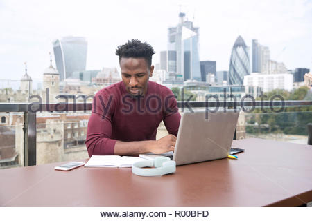 Young man using laptop on balcony - Stock Image