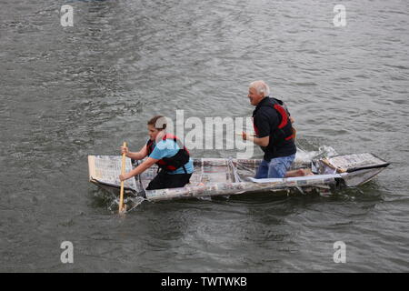 Saltash, UK. 23 June 2019. Participants paddle in the annual Cardboard Boat Race. The challenge of the event is to create a Boat made entirely of Cardboard, which can hold upto  two people and be paddled from the slipway around the bouy on the Tamar and back. Credit Julian Kemp/Alamy - Stock Image