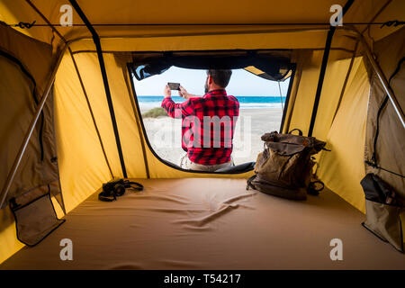Freedom traveler man outside the tent in alternative vacation lifestyle in free camping at the beach taking picture of the natura landscape - backpack - Stock Image