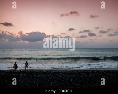 Two little children, one wearing a hat enjoy the sunset on holiday - Stock Image
