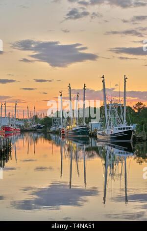 Commercial fishing boats and shrimp boats tied up at sunset in Bayou La Batre Alabama, USA. - Stock Image