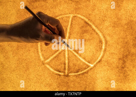 the hands of men draw in the sand the international symbol of peace. the concept of peace and good - Stock Image