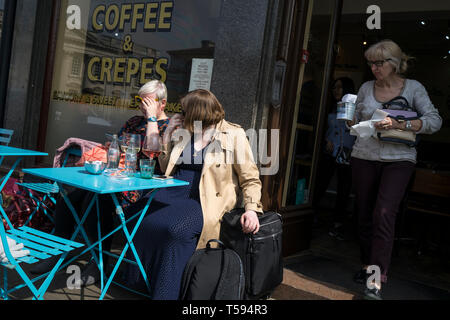 Ladies resting in sun having refreshments Coffee and Crepes Kings Parade Cambridge England 2019 - Stock Image