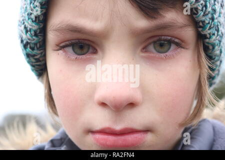 Closeup of an angry green eyed girl with a big frown - Stock Image