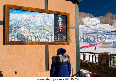 Woman looking at map of ski routs around Telluride and Mountain Village, San Miguel County, Colorado, USA - Stock Image