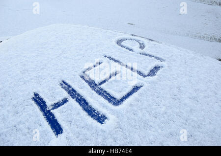 Snow covered car roof with the word help written in the snow - Stock Image