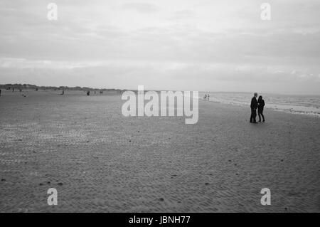 A couple standing on St Andrews beach with the tide out. - Stock Image