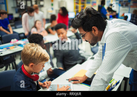 Male teacher helping junior high school boy student using digital tablet in classroom - Stock Image