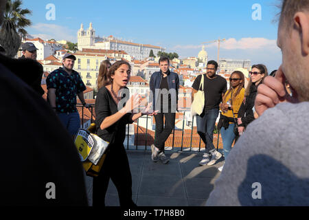 Young woman tour guide giving historical talk about Portuguese history to tourists on holiday in Alfama Lisbon Portugal Europe EU  KATHY DEWITT - Stock Image