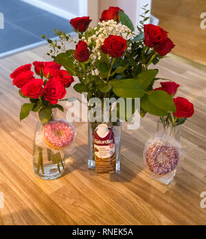 Three bunches of red roses and some treats for family on Valentine's Day - Stock Image