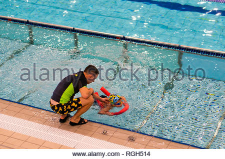 Poznan, Poland - January 26, 2019: Instruction helping boy on a swim stick during swimming lesson in a pool in the Termy Maltanskie. - Stock Image