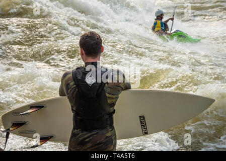 River surfer waits his turn as a freestyle kayaker rides the whitewater of the Good Wave on the Chattahoochee River in Columbus, Georgia. (USA) - Stock Image
