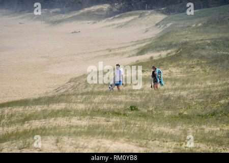 A couple walking down to the beach. - Stock Image