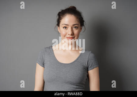 content young woman in her 20s with natural make-up and brunette hair messy bun looking pleased - Stock Image